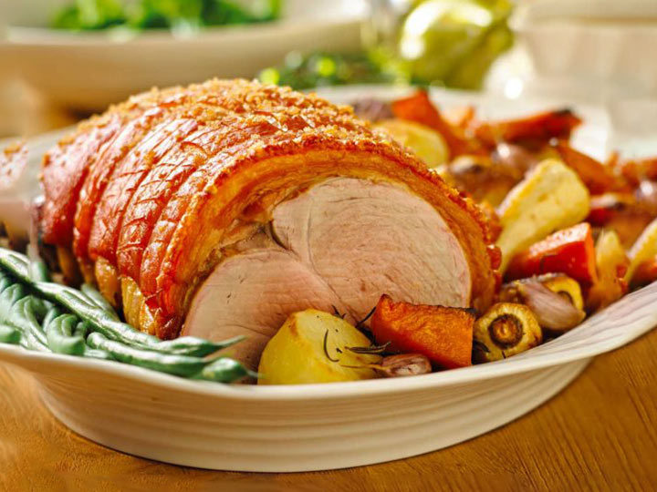 Rolled roast pork leg with crackling and roasted vegetables