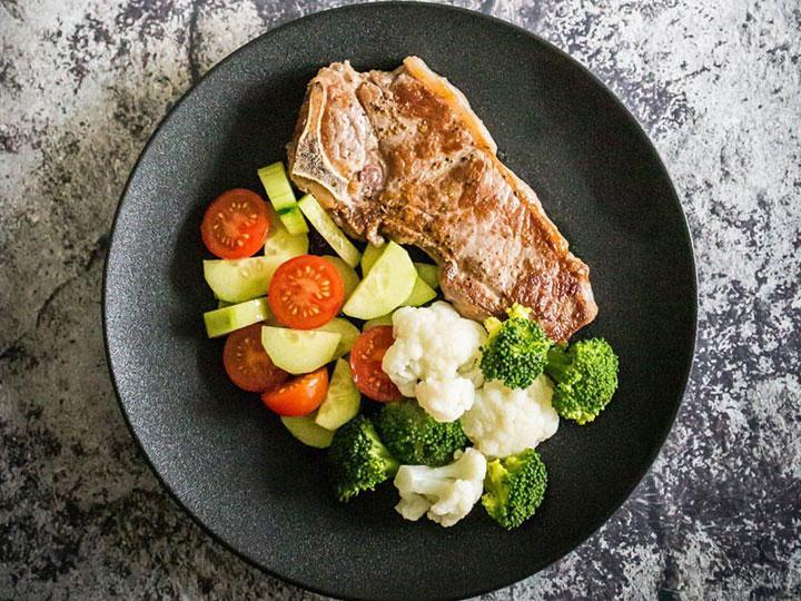 T-Bone steak with cauliflower, broccoli and tomato cucumber salad