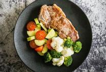 T-Bone steak with cauliflower, broccoli and tomato cucumber salad
